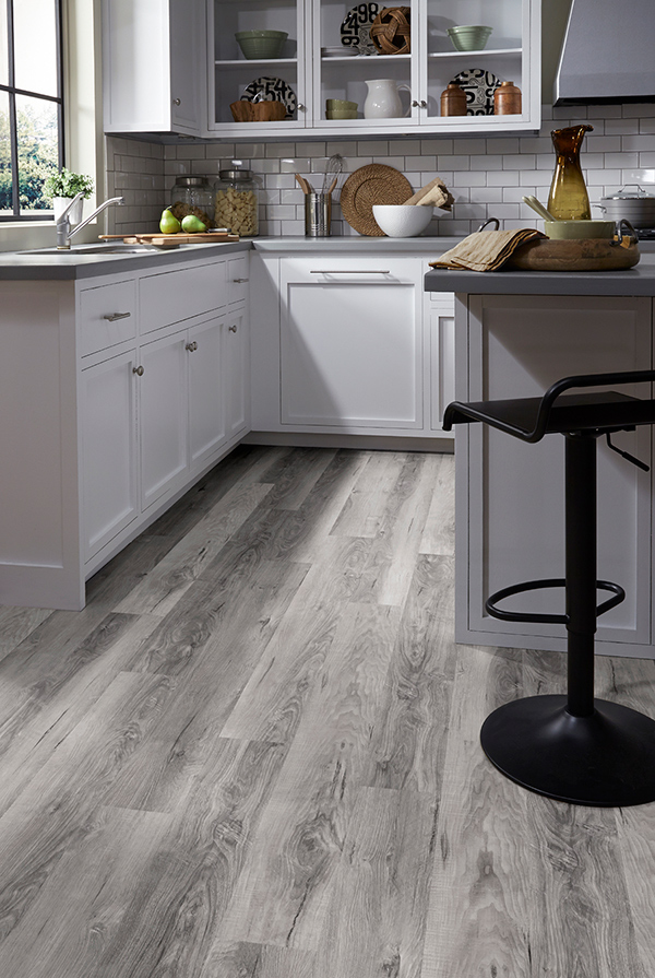 A 2020 themed kitchen with off white cabinets, grey countertops, and backsplash subway tile on trending luxury vinyl floors.